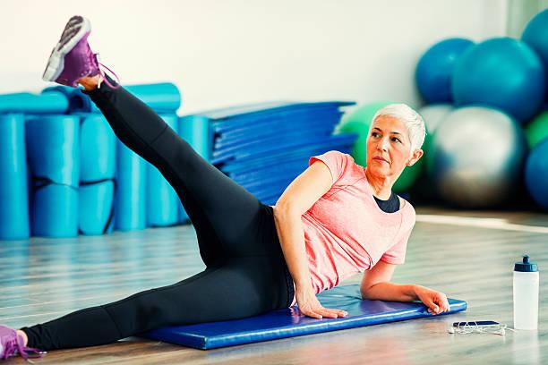 Mature Woman Exercising In Gym. - foto de stock