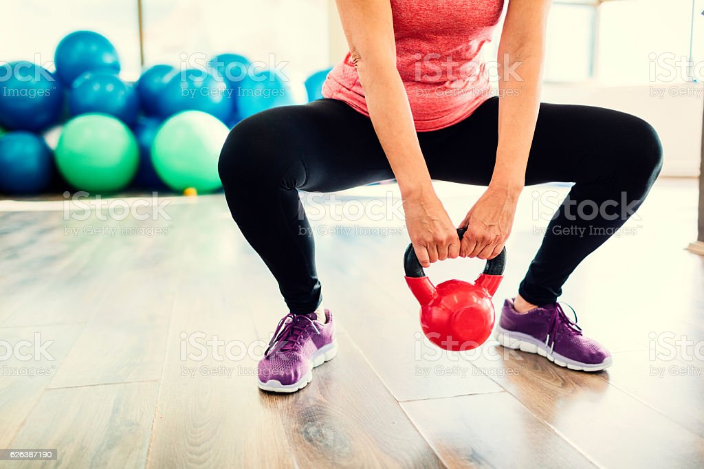 Mature Woman Exercising In Gym With Kettle Bell. stock photo