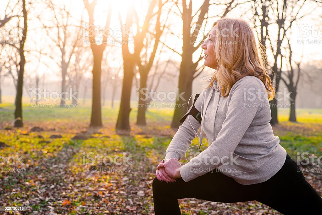 Mature woman exercising in park, stretching stock photo