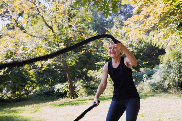 Mature woman exercising outside at the park using a rope