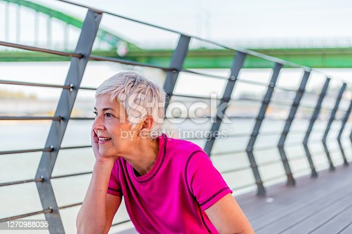 Mature woman practicing yoga outdoor exercise or doing fitness. Senior woman sitting on yoga mat.