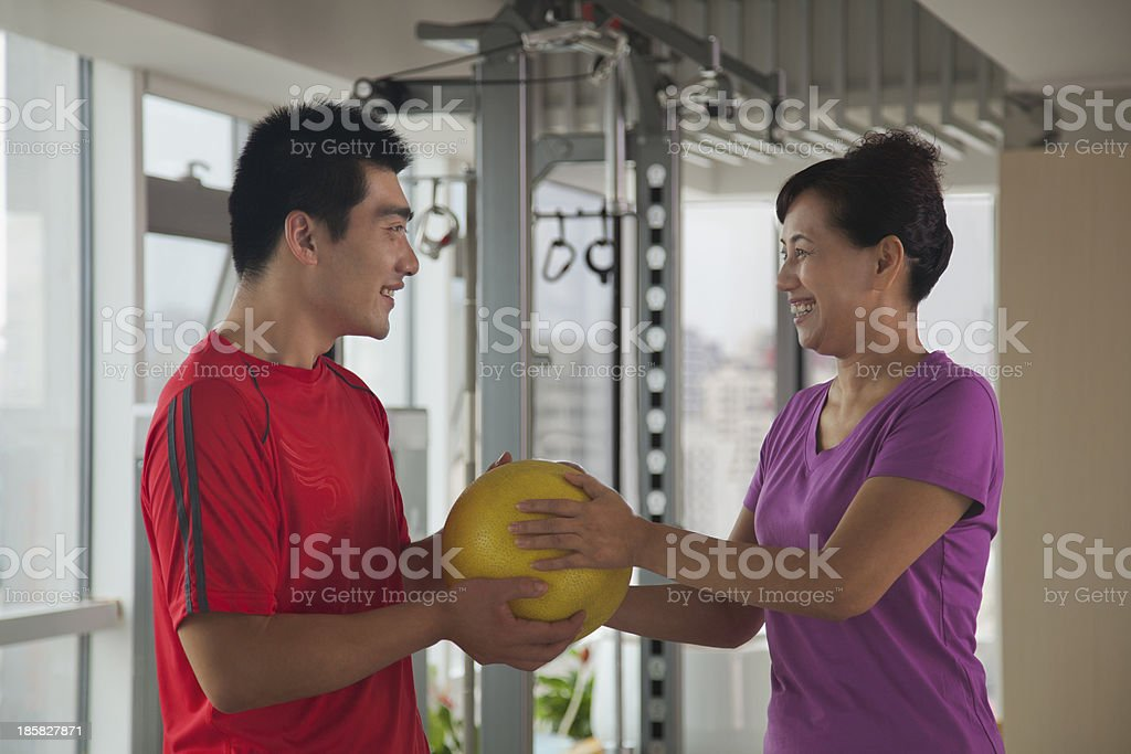 Mature woman exercising with her trainer royalty-free stock photo