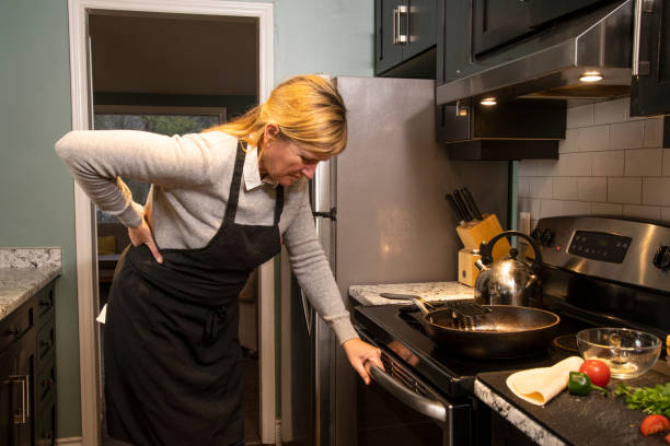 A mature woman experiencing backache at home in the kitchen stock photo