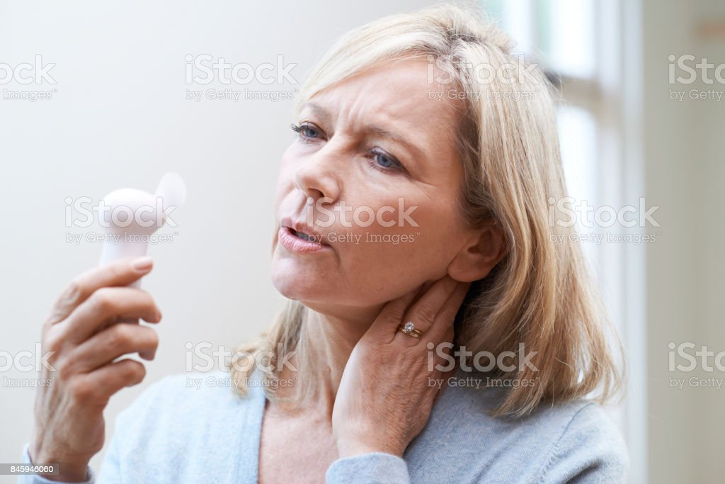 Mature Woman Experiencing Hot Flush From Menopause - Foto stock royalty-free di Adulto