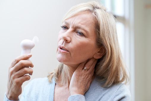 Mature Woman Experiencing Hot Flush From Menopause - Fotografie stock e altre immagini di Adulto