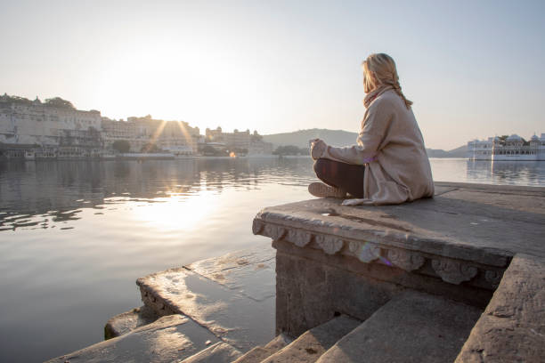 Mature woman explores a ghat at sunrise, looks out across lake Lake Pichola, Udaipur lake palace stock pictures, royalty-free photos & images