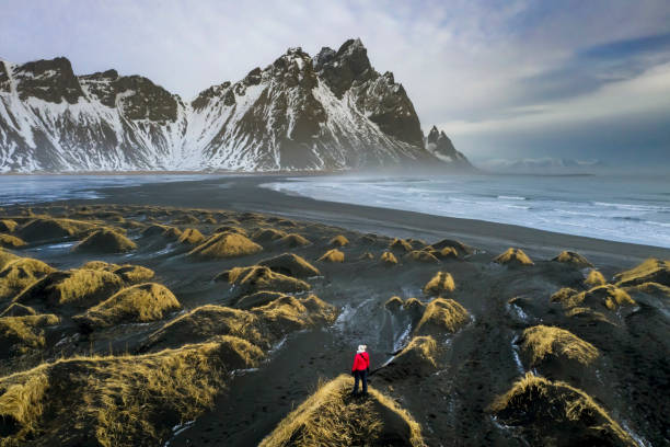 Mature woman exploring Stokksnes with Vestrahorn mountain in the background Mature woman exploring Stokksnes with Vestrahorn mountain in the background, Iceland. black sand stock pictures, royalty-free photos & images