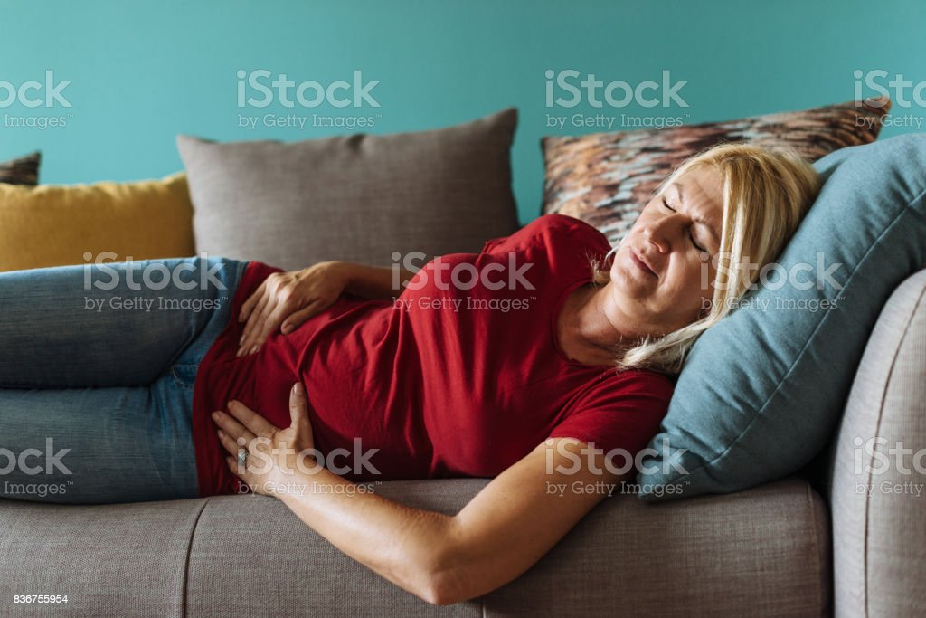 Mature woman facing pelvic pain at home stock photo