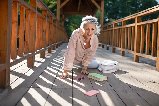 istock Mature woman falling down on the bridge while feeling unwell 1178592776