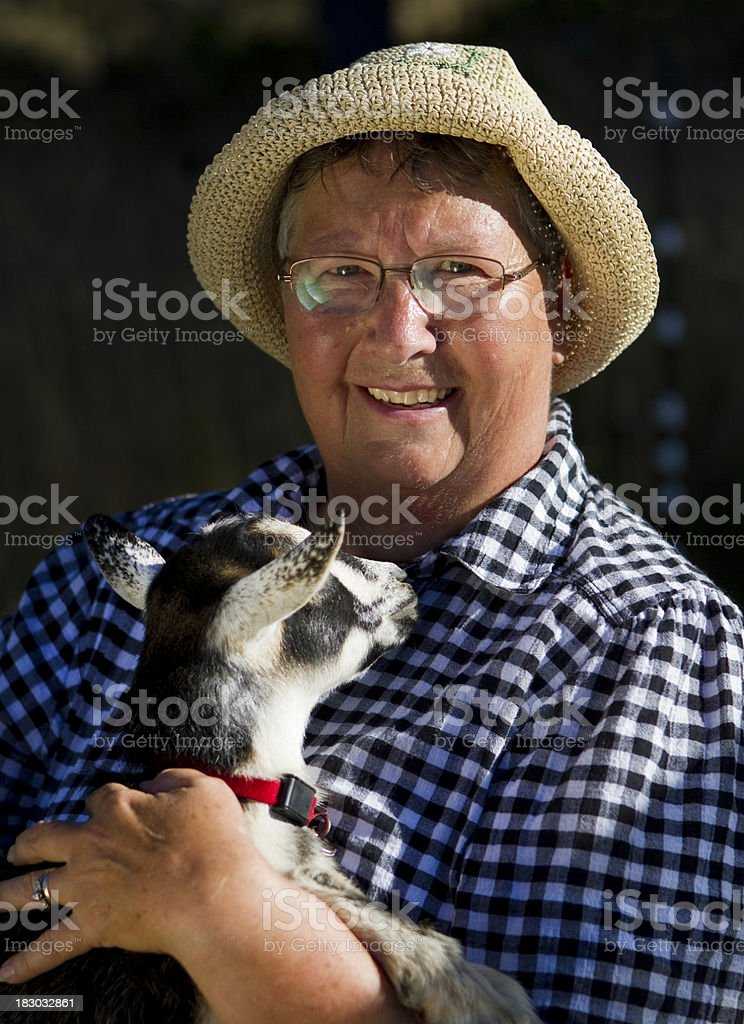 Mature Woman Farmer Holding a Baby Goat stock photo