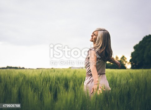 Beautiful mature woman dancing and feeling youthful while in a lush green summer field in a large park