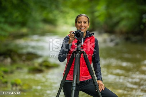 telephoto shot of professional outdoor photographer smiling female woman shallow depth of focus on smiling woman with camera tripod closer view