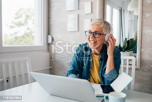 Mature woman with headphones working online from her home.