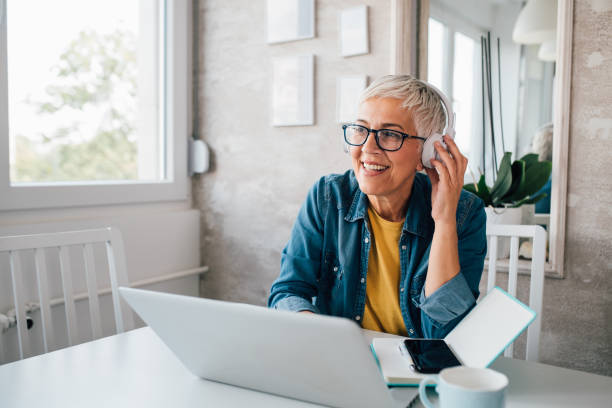 Mature woman freelancing from her home office stock photo