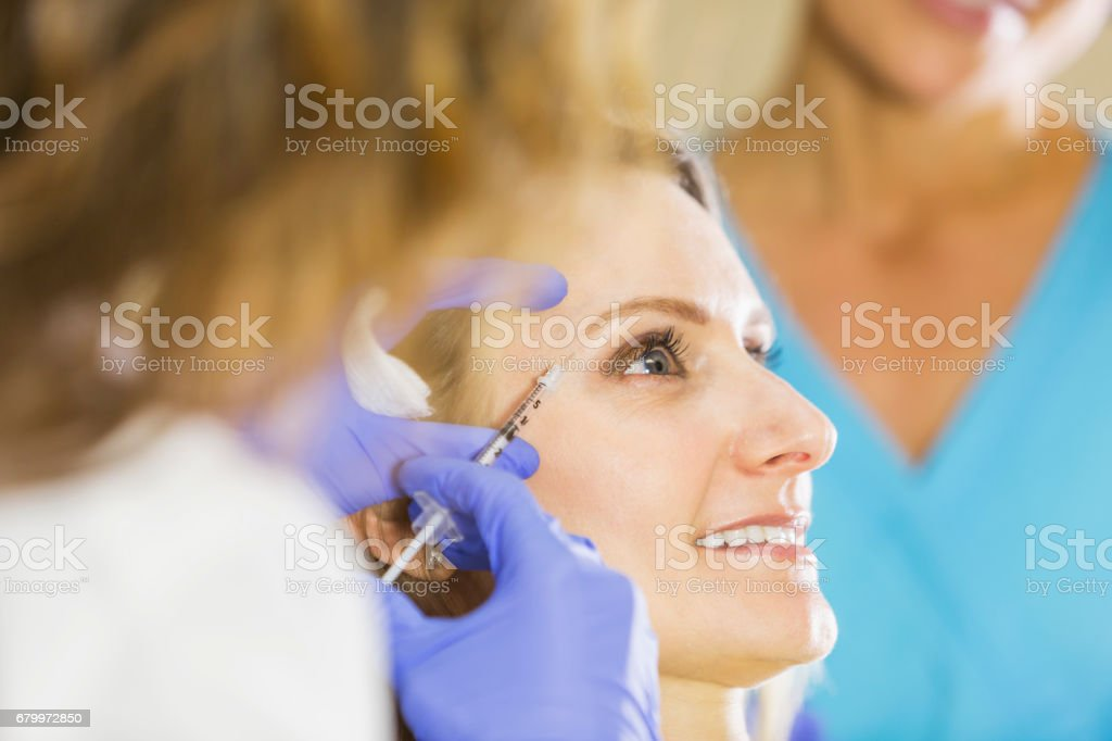 Mature woman getting injection for wrinkle treatment stock photo