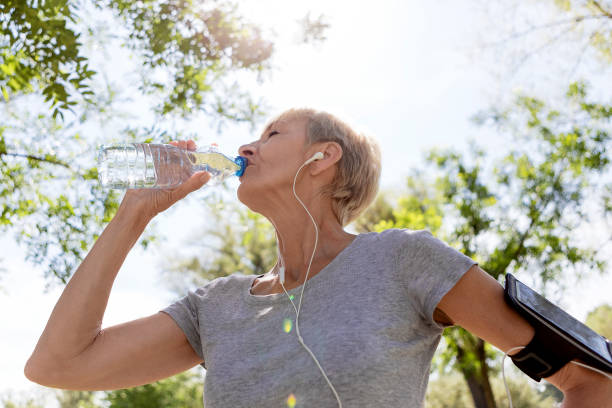 reife frau, die immer nach laufen aktualisiert - armband water stock-fotos und bilder