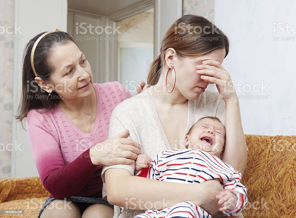Mature woman gives solace to crying adult daughter stock photo