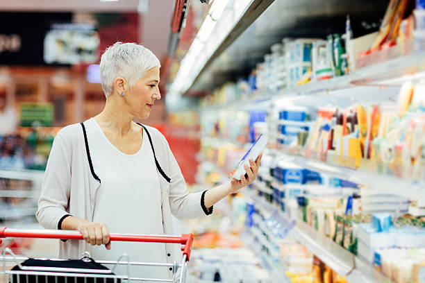 mature woman groceries shopping. - nutrition label stock photos and pictures