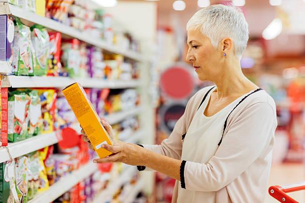 mature woman groceries shopping. - ingrediënt stockfoto's en -beelden