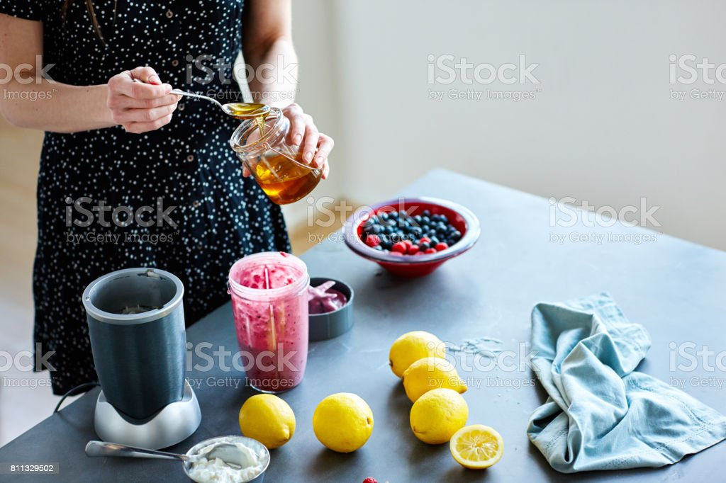 Mature woman hands preparing a smoothie stock photo