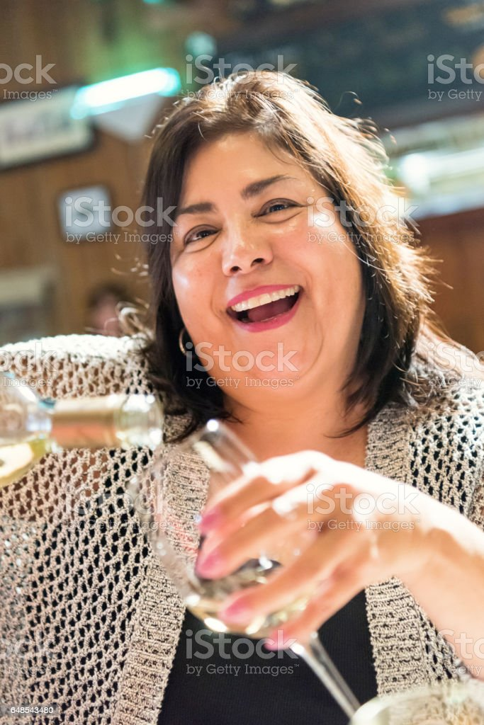 Mature woman having a glass of wine in a tavern stock photo