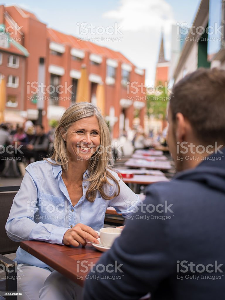 Mature woman having an outdoor coffee with her son stock photo