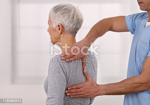 istock Mature Woman having chiropractic back adjustment. Osteopathy, Physiotherapy, Sport injury rehabilitation concept, holistic care 1132352012