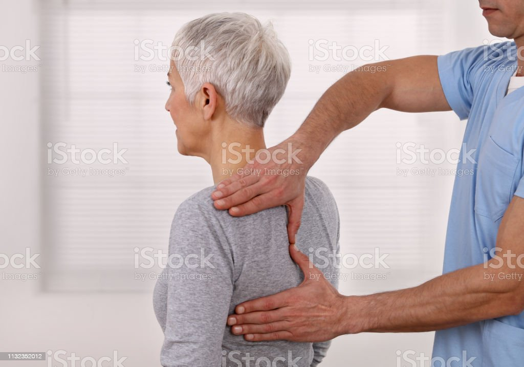 Mature Woman having chiropractic back adjustment. Osteopathy, Physiotherapy, Sport injury rehabilitation concept, holistic care stock photo