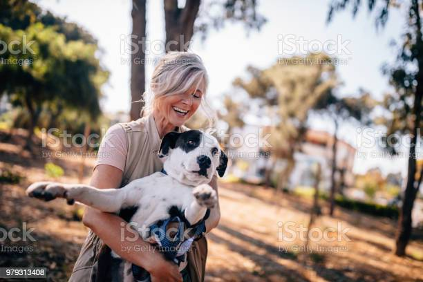 Mature woman having fun playing with pet dog in park picture id979313408?b=1&k=6&m=979313408&s=612x612&h=l1dxcav4dd27ua6lqzyrot7y1ptjq3fdv8d1hbh ows=