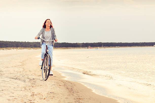 ältere frau, die spaß mit dem fahrrad am strand - wellness ostsee stock-fotos und bilder