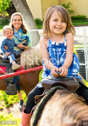 Smiling caucasian mature woman posing with her children riding ponies in a county fair