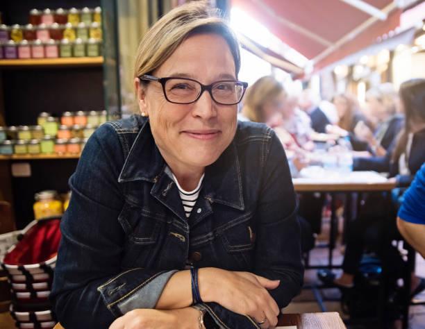 mature woman having lunch in small outdoor restaurant. - showus стоковые фото и изображения