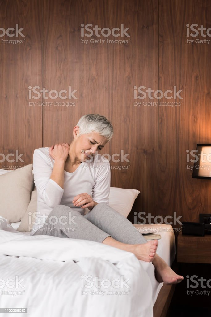 Stressed senior woman waking up with uncomfortable neck pain in her...