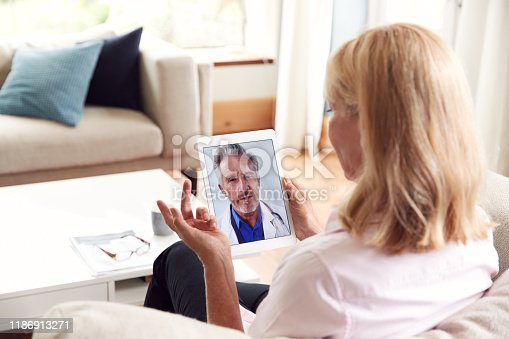 Mature Woman Having Online Consultation With Doctor At Home On Digital Tablet