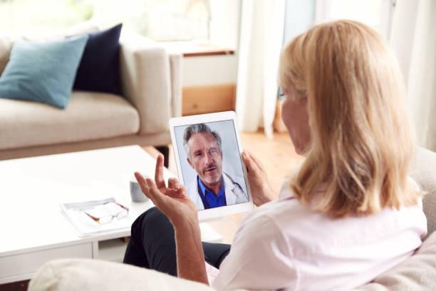 mujer madura tener consulta en línea con el médico en casa en la tableta digital - telehealth fotografías e imágenes de stock