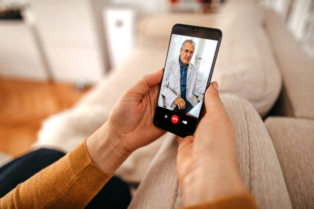 Mature woman having online consultation with doctor at home on smartphone stock photo