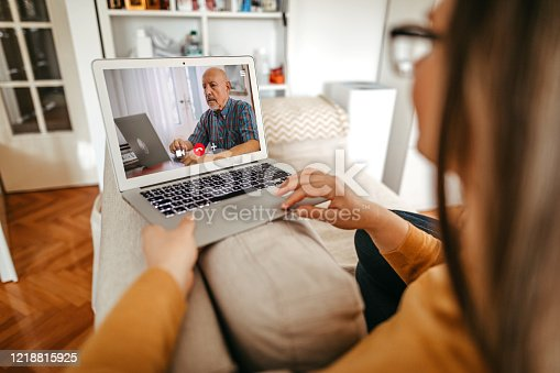 Mature woman having online consultation with psychotherapist at home on laptop