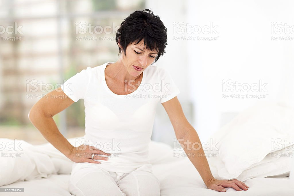 mature woman having stomach ache stock photo