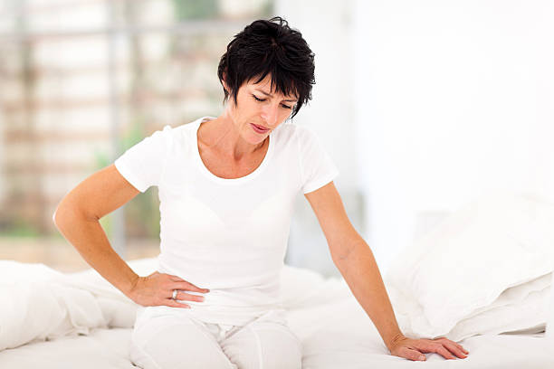 mature woman having stomach ache - stomach sitting stock photos and pictures