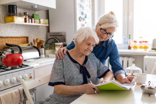 mature woman helping elderly mother with paperwork - filhos adultos imagens e fotografias de stock