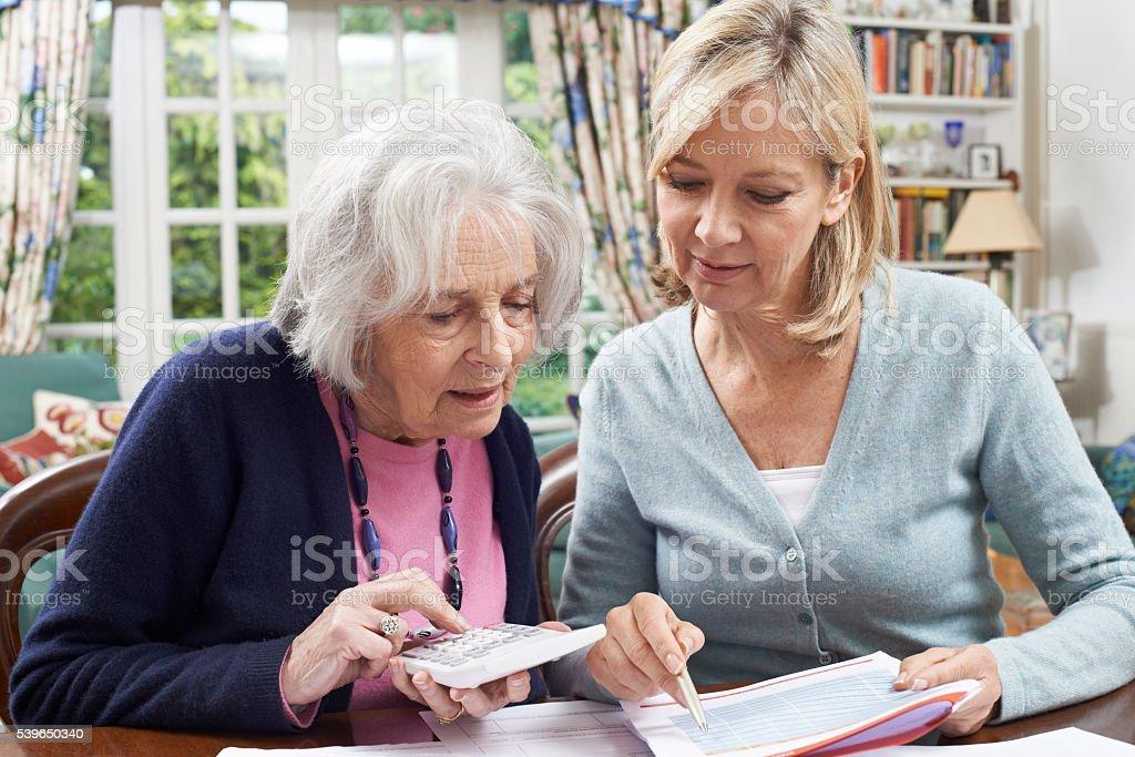 Mature Woman Helping Senior Neighbor With Home Finances stock photo