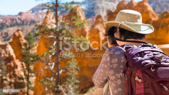 mature asian woman hiking Bryce Canyon National Park. Woman taking a photograph.
