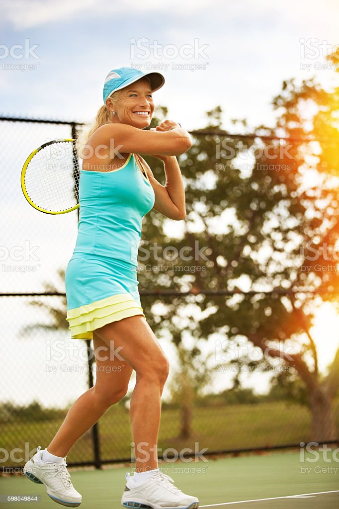 Mature woman hitting forehand winner stock photo