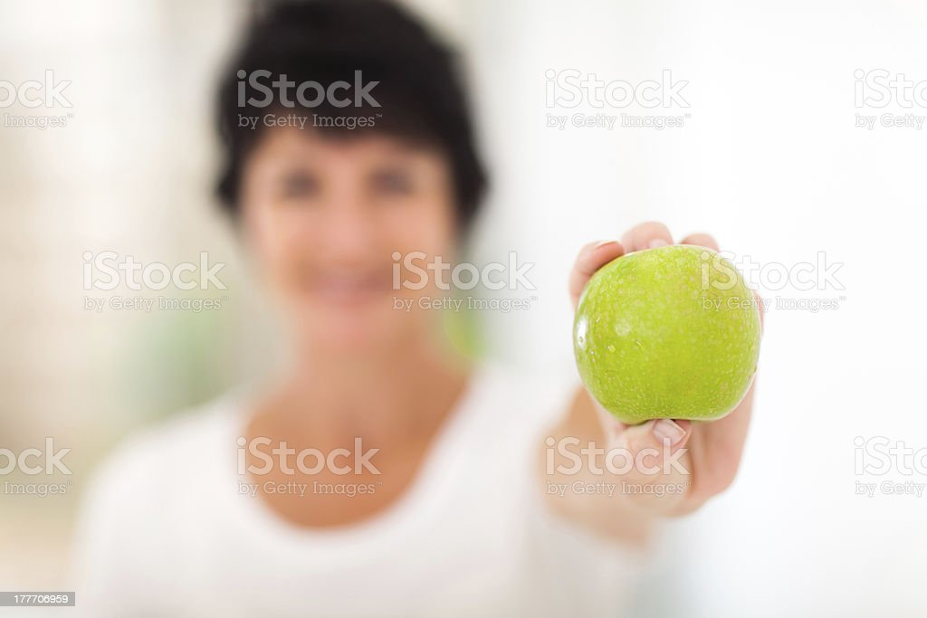 mature woman holding a green apple royalty-free stock photo