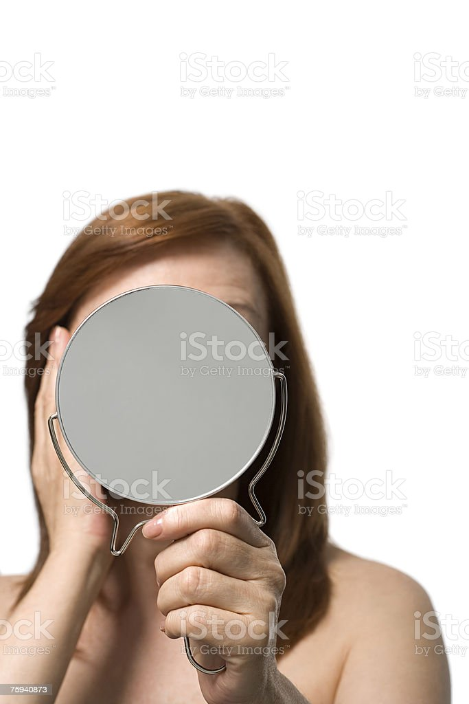 Mature woman holding a hand mirror stock photo