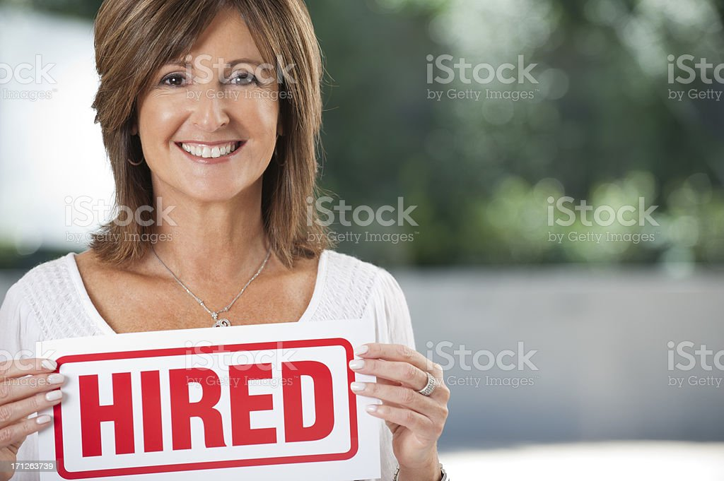 Mature woman holding a hired sign stock photo