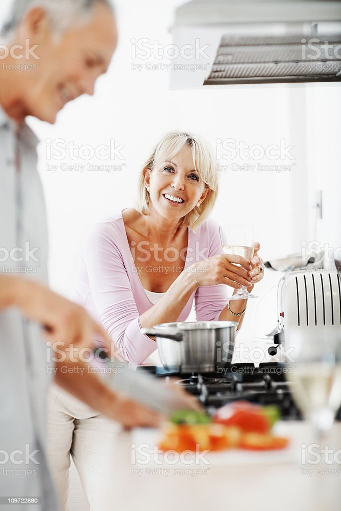 Mature woman holding champagne flute with man in a kitchen royalty-free stock photo