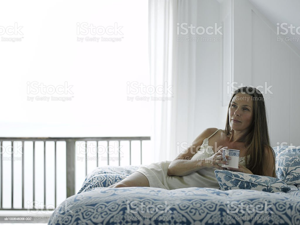 Mature woman holding coffee cup on bed royalty free stockfoto