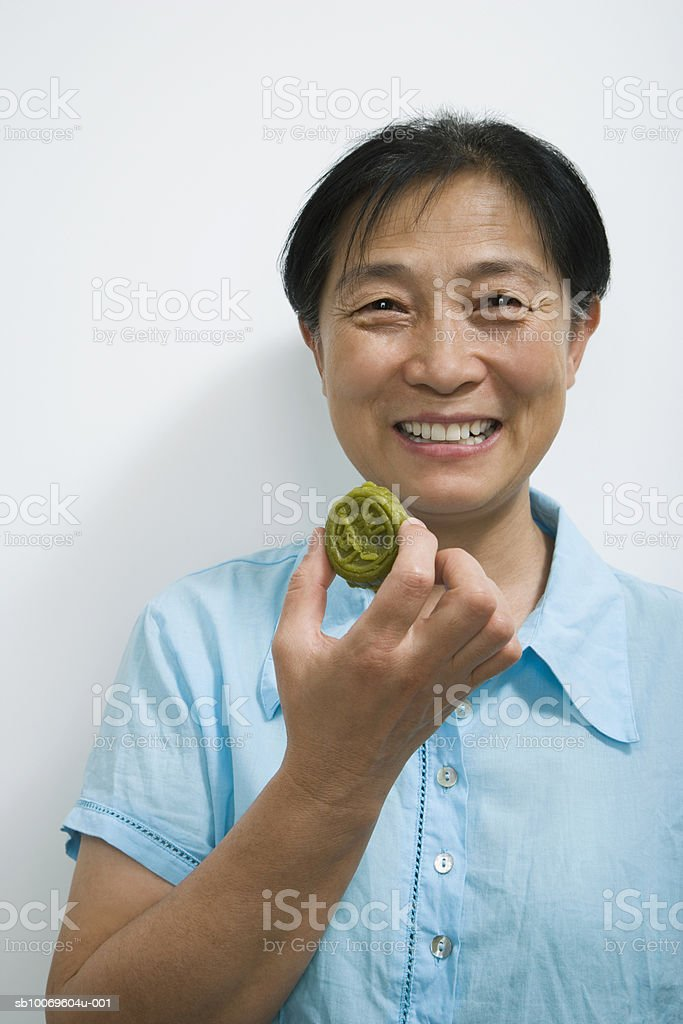 Mature woman holding cookie indoors, portrait 免版稅 stock photo