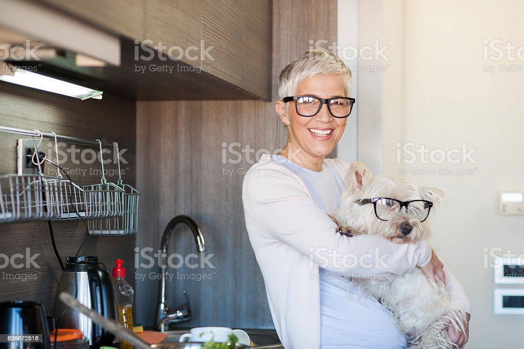 Mature woman holding dog at home - Photo